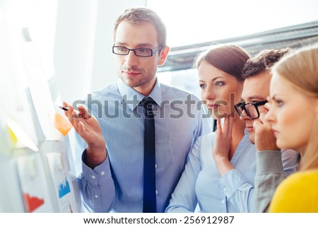 Sales representatives in a meeting with their manager and comparing their sales - stock photo