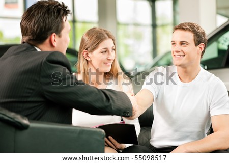 Sales situation in a car dealership, the dealer is shaking hands with a young couple, they want the car in the background - stock photo