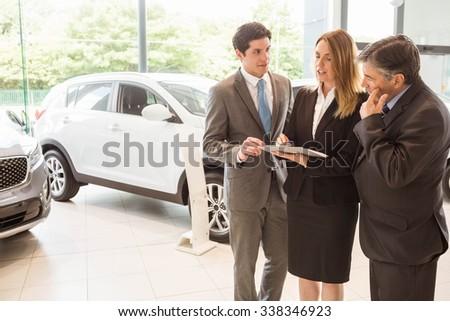 Sales team look at a clipboard at new car showroom - stock photo