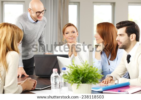 Sales team with laptop working on project while sitting at office. Teamwork. - stock photo