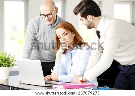 Sales team working with laptop while sitting at meeting.  - stock photo