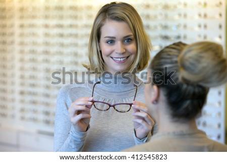 Salesgirl Assisting Customer To In Wearing Glasses - stock photo