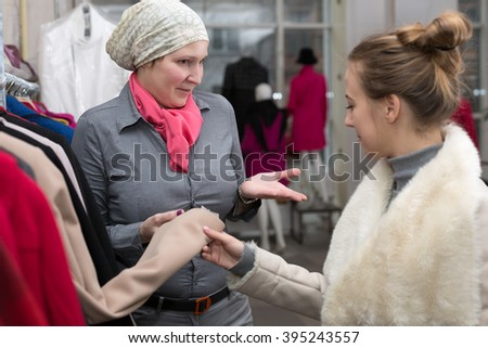 Saleslady in Uniform showing Variety of Winter and Spring Jackets to young Female Customer in Retail Store explaining features and trying to get a deal - stock photo
