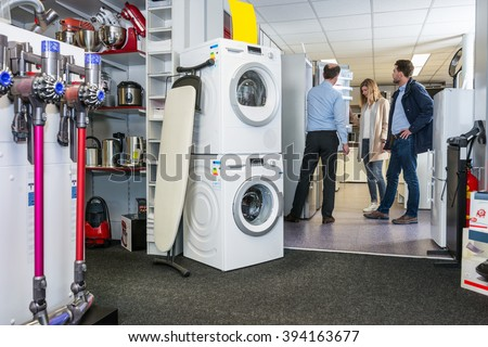 Salesman assisting couple in buying refrigerator at electronics shop - stock photo