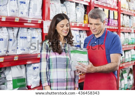 Salesman Assisting Customer In Buying Pet Food At Store - stock photo
