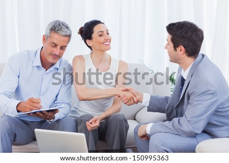 Salesman closing a deal with a couple sitting on couch - stock photo