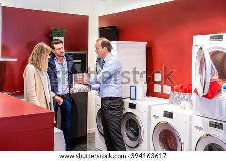 Salesman explaining product to couple in washing machine department at electronics shop - stock photo