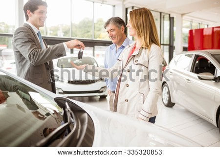 Salesman giving car key to a couple at new car showroom - stock photo