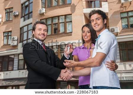 Salesman giving keys to property owners. Handshake deal with young couple outside and looking into camera - stock photo