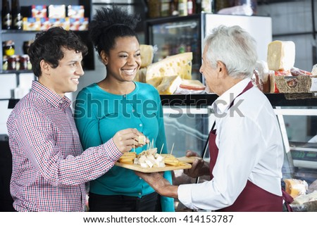 Salesman Offering Cheese Samples To Customers In Shop - stock photo