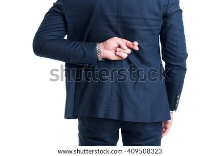 Salesman or businessman making fingers crossed good luck gesture behind back - stock photo