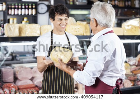 Salesman Receiving Cheese From Colleague In Shop - stock photo
