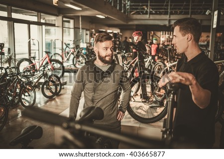Salesman showing a new bicycle to interested customer in bike shop. - stock photo