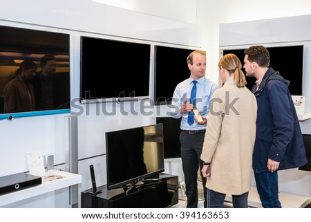 Salesman showing flat screen television to young couple in electronics store - stock photo
