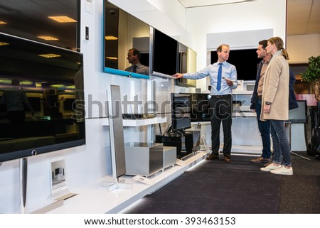 Salesman showing flat screen TV to young couple in electronics store - stock photo