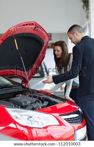 Salesman showing the car engine in a garage - stock photo