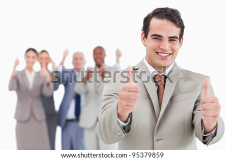 Salesman with team behind him giving thumps up against a white background - stock photo