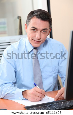 Salesman working in front of computer - stock photo