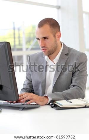 Salesman working on desktop computer - stock photo