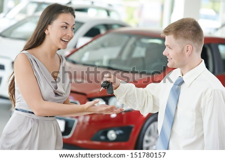 salesperson demonstrating new automobile car to young woman - stock photo
