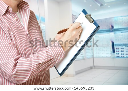 Salesperson in optician store holding a clipboard and taking a notes with pen - stock photo