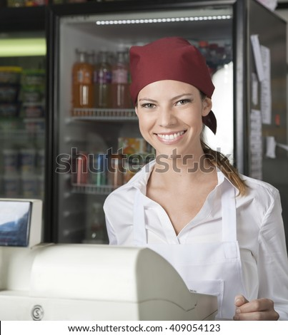 Saleswoman At Checkout Counter In Grocery Store - stock photo