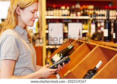Saleswoman counting wine bottles with mobile data registration terminal - stock photo