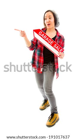 Saleswoman holding a Garage sale sign and pointing - stock photo