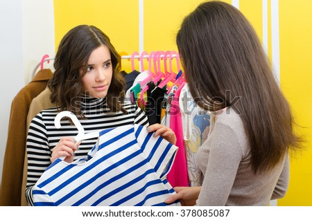 Saleswoman showing clothes to the young female customer.  - stock photo