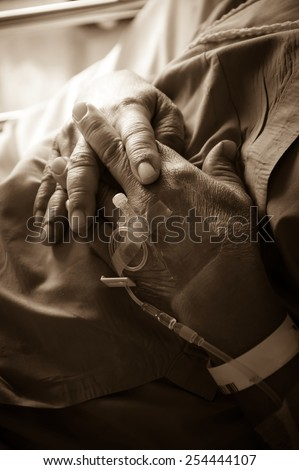 Saline intravenous solution in a patients hand,sepia color. - stock photo