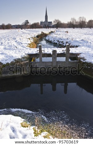 Salisbury cathedral and the water meadows during some January snow. - stock photo