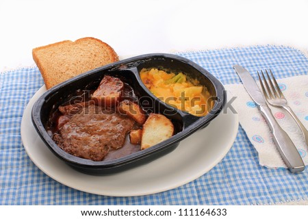 Salisbury steak and potatoes TV dinner in plastic dish on white plate against blue gingham place mat. - stock photo