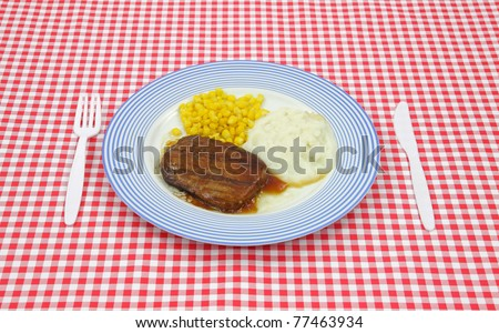 Salisbury steak meal with corn and potato on a blue striped plate with plastic silverware on a red checkerboard cloth. - stock photo