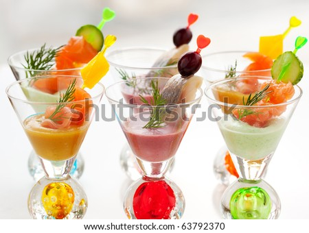 Salmon and herring appetizers in glasses with three different  sauce(mustard,wasabi and cranberry sauce) - stock photo