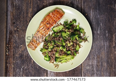 Salmon and Rice. Wild Caught Alaskan Salmon, Wild Rice and Fresh Broccoli Dinner Plate on Vintage Wood Table. - stock photo