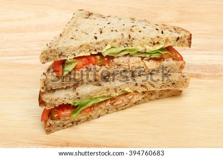 Salmon and salad sandwiches made with multi seeded brown bread on a wooden board - stock photo