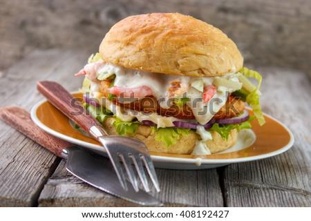 Salmon and shrimp burger , mayonnaise on bottom bun , breaded salmon shrimp patty and tartar sauce with fresh shrimps on gray wooden boards background - stock photo