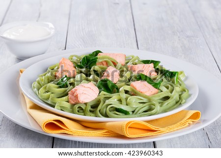 salmon and spinach fettuccine pasta on white dish and table napkin, cream sauce in a gravy boat on a wooden italian style, close-up  - stock photo