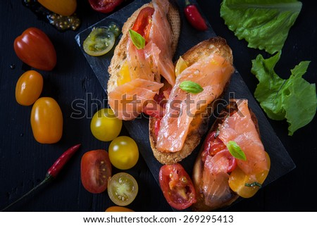 salmon bruschetta with cherry tomato and chili pepper - stock photo