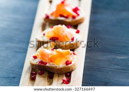 Salmon bruschetta with white cheese and pomegranates on wooden kitchen board over dark wooden background - stock photo
