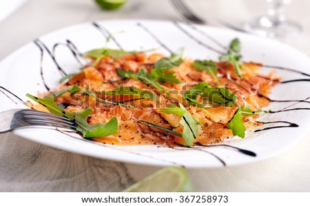 Salmon carpaccio close up with arugula leaves on it, fork near it on neutral wooden background - stock photo