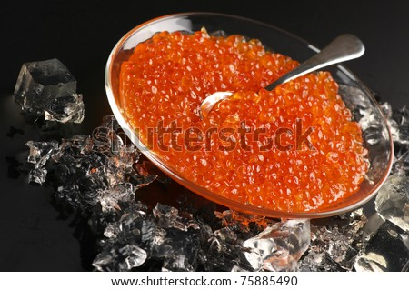 Salmon caviar in glass plate with spoon and ice on black background. - stock photo