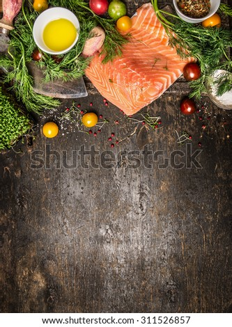 Salmon  fillet and ingredients for cooking on dark rustic wooden background, top view. Healthy food cooking concept. - stock photo