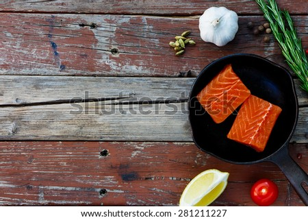 Salmon fillet on vintage cast iron skillet with ingredients over rustic wooden background. Vegetarian food, health or cooking concept. Space for text. - stock photo