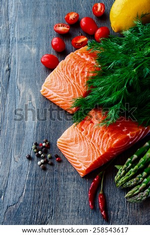 Salmon fillet with asparagus and aromatic herbs, spices and vegetables over wood - healthy food, diet or cooking concept.  - stock photo