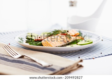 salmon fillet with asparagus in a dish with a blue border and a blue stripe placemat - stock photo