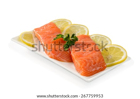Salmon fillets with lemon slices on a white background  - stock photo