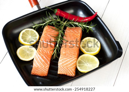 Salmon fish with fresh herbs, lemon and pepper - stock photo