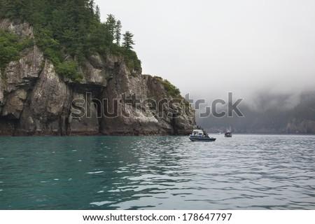 Salmon fishing boats along the shore cliffs near Seward, Alaska - stock photo