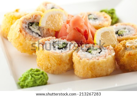 Salmon Fried Maki Sushi - Hot Roll with Cream Cheese and Cucumber inside. Deep Fried Salmon outside. - stock photo